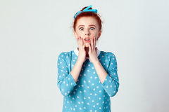 Redhead young girl touching her cheeks and looking at camera with shocked face. Human face expressions and emotions. Redhead young girl touching her cheeks and stock images