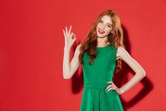Redhead young happy lady in green dress showing okay gesture. Photo of redhead young happy lady in green dress standing over red wall background looking camera Royalty Free Stock Photography