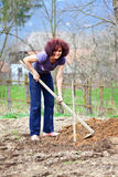 Redhead young lady digging in the garden Royalty Free Stock Images