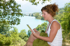 Redhead young woman with a digital tablet. Redhead young woman sitting with a digital tablet in nature Stock Images