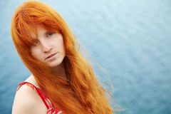 Redhead young woman in a dress on the ocean coast Stock Images