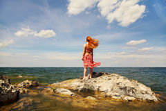 Redhead young woman in a dress on the ocean coast Royalty Free Stock Image