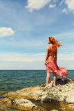Redhead young woman in a dress on the ocean coast Royalty Free Stock Photography