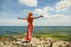 Redhead young woman in a dress on the ocean coast Stock Photo