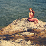 Redhead young woman in a dress on the ocean coast Royalty Free Stock Images