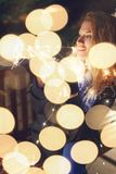 Redhead young woman holding fairy lights in park at winter, sitting on bench, bokeh royalty free stock images