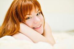 Redhead young woman laying in bed Stock Image