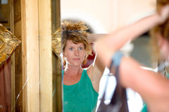 Redhead young woman looking into a mirror. And headdress Royalty Free Stock Images