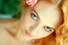 Redhead young woman outdoors. Romantic young woman face close up outdoors at a summer day. Soft summer colors Royalty Free Stock Photo