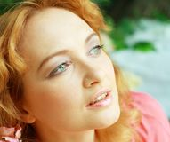Redhead young woman outdoors. Romantic young woman face close up outdoors at a summer day. Soft summer colors Royalty Free Stock Photos