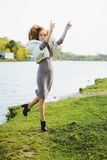 Redhead young woman walking in autumn park near water Royalty Free Stock Photo