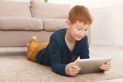 Redheaded мальчик играя на цифровом планшете на ковре стоковые фото
