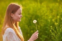 Redheaded предназначенная для подростков девушка дуя на одуванчиках Стоковые Изображения RF