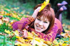 Redheaded autumn. Happy redheaded girl laying on the leaves in autumn forest royalty free stock photos