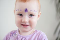 Redheaded baby with rhinestones. On face Stock Images