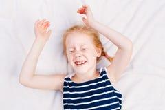 redheaded Caucasian barnflicka i randigt nautiskt sleeveless sova för skjorta arkivbilder