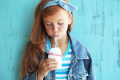 Redheaded child. Cute redheaded child drinking milk on vintage blue background royalty free stock photography
