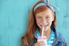 Redheaded child. Cute redheaded child drinking milk on vintage blue background royalty free stock photo