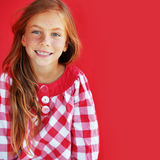 Redheaded child. Cute redheaded child on red background stock image
