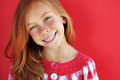 Redheaded child. Cute redheaded child on red background royalty free stock image