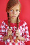 Redheaded child. Cute redheaded child on red background Royalty Free Stock Photo