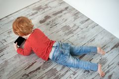 The redheaded child lies on the floor. And looks at the cartoon in the phone Royalty Free Stock Photos