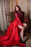 Redheaded dziewczyna w czerwonej sukni w wnętrzu zdjęcie royalty free