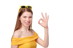 Redheaded female in yellow gesturing OK Royalty Free Stock Images