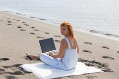 Redheaded flicka som arbetar på ett bärbar datorsammanträde på Arkivbild