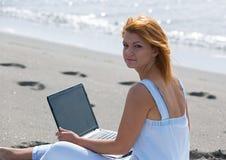 Redheaded flicka som arbetar på ett bärbar datorsammanträde på Royaltyfri Bild