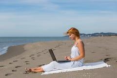 Redheaded flicka som arbetar på ett bärbar datorsammanträde på Royaltyfria Foton