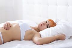 Redheaded Frau im Schlafzimmer Stockfotografie