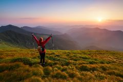 Redheaded girl athlete with a backpack and sticks stands on the green hillocks and looks at high mountain landscapes. Redheaded girl athlete with a backpack and Stock Photography
