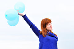 Redheaded girl with balloons Stock Photos