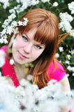 Redheaded girl in blossom. Beautiful redheaded girl standing in the tree blossom Stock Images