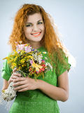 Redheaded girl with bouquet. Young redheaded girl with bouquet of summer flowers Royalty Free Stock Photography