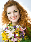 Redheaded girl with bouquet. Young redheaded girl with bouquet of summer flowers Royalty Free Stock Images