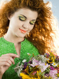 Redheaded girl with bouquet. Young redheaded girl with bouquet of summer flowers Stock Images