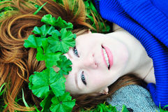Redheaded girl with crown from leaves. Face and shoulders of redheaded girl laying on the green grass with crown from leaves Stock Photography