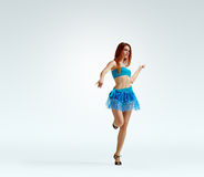 Redheaded girl in dance. Young beautiful dancer in bright dress on light studio background Royalty Free Stock Image