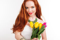 Redheaded girl with freckles is holding tulips. Beautiful redheaded girl with freckles on her face bouquet of colorful tulips Stock Image