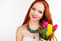 Redheaded girl with freckles is holding tulips. Beautiful redheaded girl with freckles on her face bouquet of colorful tulips Stock Photos