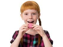 Redheaded girl with freckles opened her mouth and wants to eat macaron pink cak Stock Images