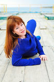 Redheaded girl laying on the pier Stock Photography