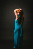 Redheaded girl in a long blue dress in the studio. Beautiful redheaded girl in a long blue dress in the Studio Stock Photo