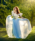 Redheaded girl in a long dress. Outdoors Royalty Free Stock Image