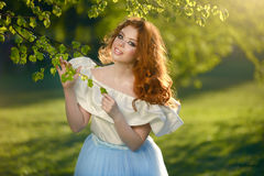 Redheaded girl in a long dress. Outdoors Stock Image