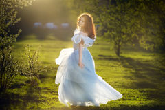 Redheaded girl in a long dress. Outdoors Stock Images