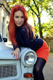 Redheaded girl near car Stock Photos