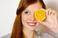 Redheaded  girl with orange Royalty Free Stock Images